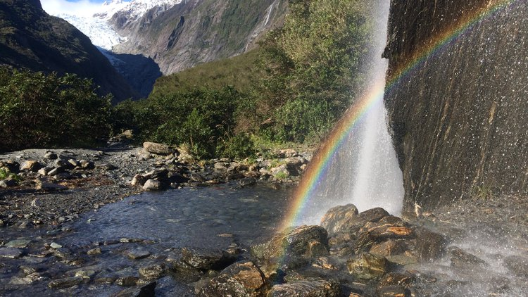 Rainbows in Trident Falls waterfall in the Franz Josef Glacier Valley