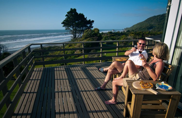 Guests enjoying homemade pizza on the deck with views to Tasman Sea