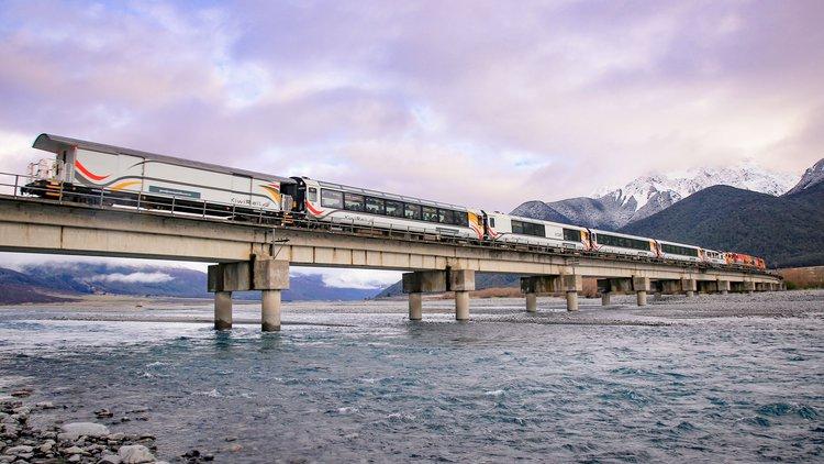 TranzAlpine train crossing a wintry Waimakariri River high in the Southern Alps near Cass.